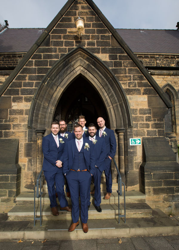 Grrom and groomsmen on the steps up to the church st thomas and st james church worsbrough barnsley
