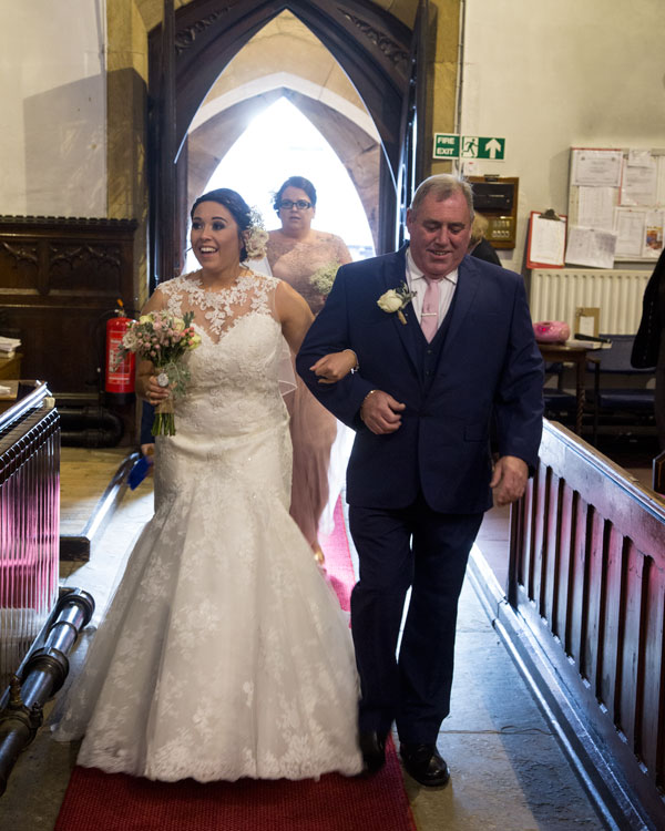 Bridesmiling at groom while walking down the aisle south yorkshire photographer