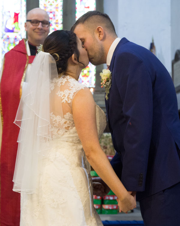 Bride and groom kiss during church wedding ceremony barnsley photographer