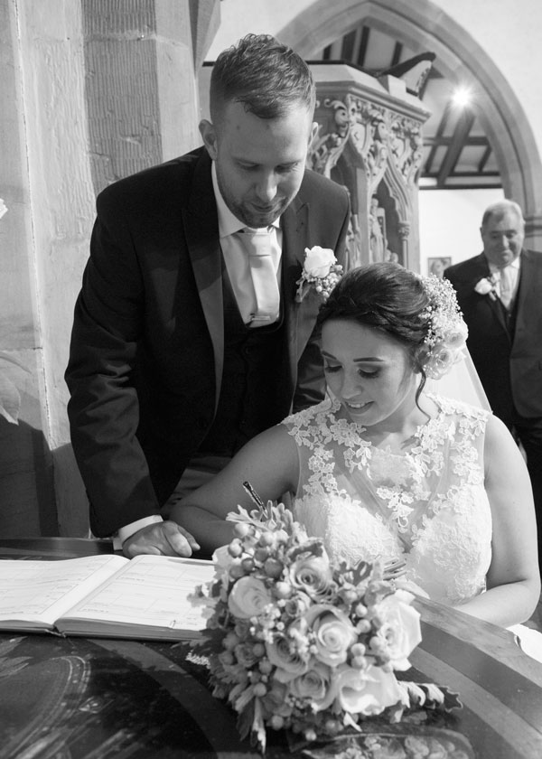 Bride and groom signing the register in st thomas and st james church worsbrough barnsley photographer
