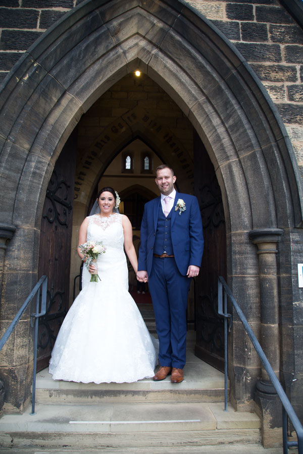 Bride and groom standing on the church steps after the wedding st thomas and st james church worsbrough barnsley photographer