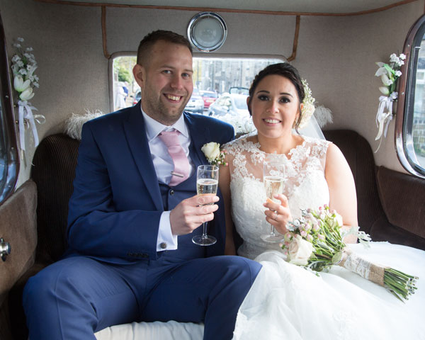 bride and groom drinking champagne in the back of their wedding car