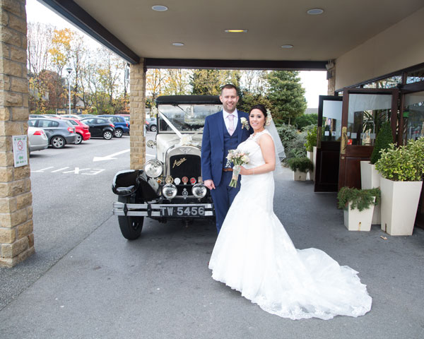 newlyweds in front of the wedding car outside holiday inn barnsley photographer