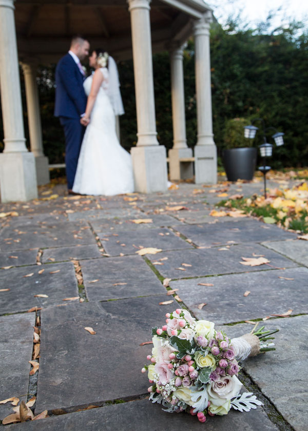 Bride and groom kissing under archway in secret garden holiday inn barnsley photographer bouquet in foreground