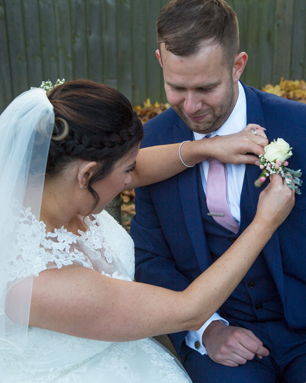 Bride fixing grooms buttonhole on stone bench in secret garden holiday inn barnsley photographer