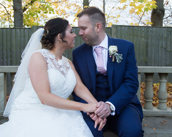 Bride and groom looking at each other on stonbe bench holiday inn barnsley photographer