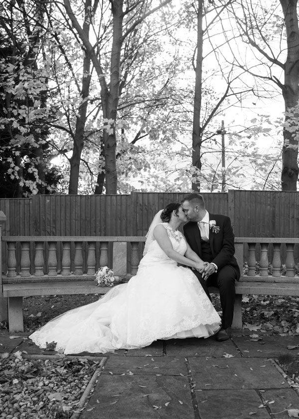 bride and groom kissing on stone bench in secret garnden holiday inn barnsley photographer