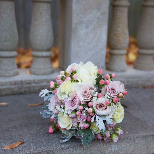 dusky pink bridal bouquet on stone bench in secret garden holiday inn barnsley photographer