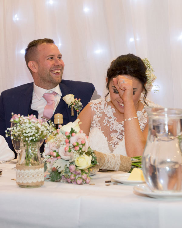 groom andbride laughing attop table in front of twinkle backdrop holiday inn barnsley photographer