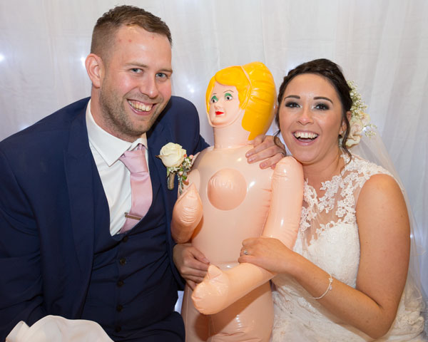 Bride and groom holding and smiling with blow up doll in front of twinkle backdrop holiday inn barnsley photographer