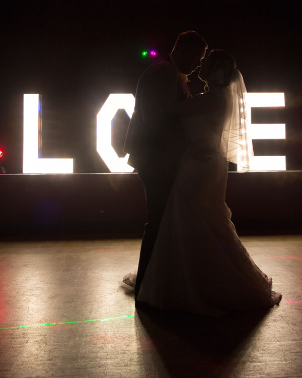 bride and groom first dance with love light up letters on stage in background holiday inn barnsley scarletts bar