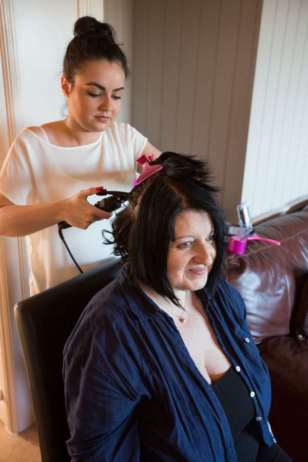 Bride with black hair having hair curled by the hairdresser