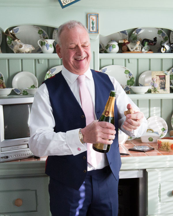 Father of the groom opening a bottle of champagne in a green kitchen on the morning of the weddng