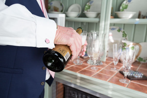 Groomsman in white shirt with pink cufflinks pouring champagne in the morning if the wedding