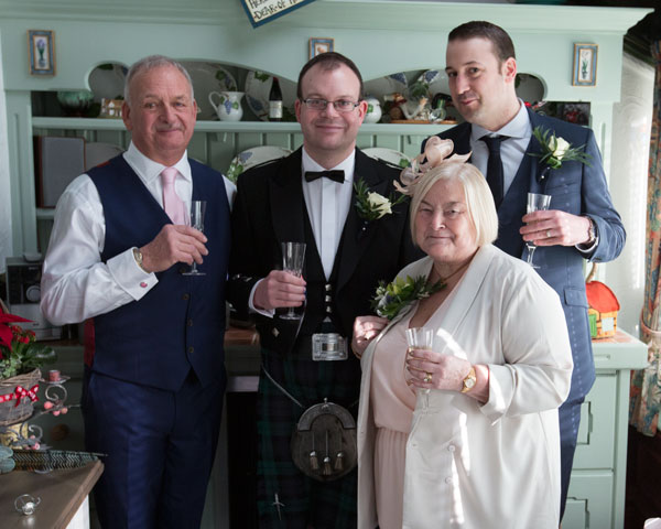 Groom with his father, best man and mother drinking champagne in their kitchen Adwick upon Dearne wedding photographer