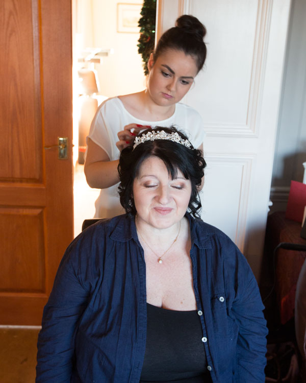 Bride with hairdresser putting in sparkly tiara in curled hair in brides home adwick upon dearne