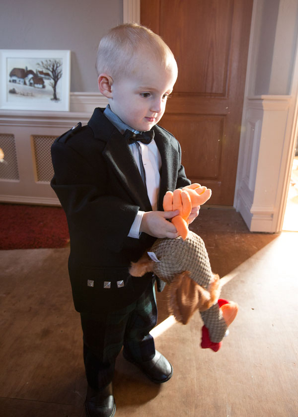 Page boy playing with toy chicken in his wedding suit