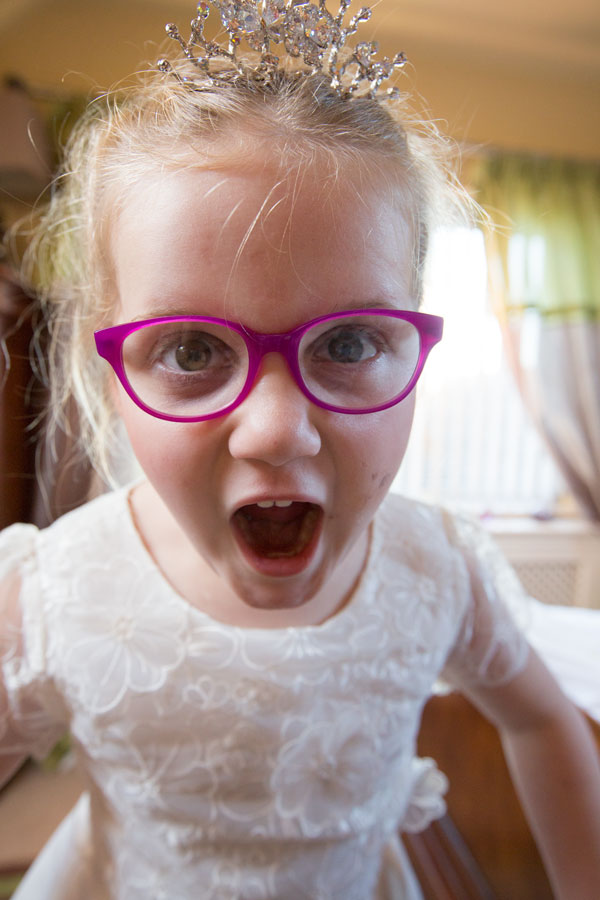 Bridesmaid with tiara and pink glasses with mouth open leaning towards camera in her white bridesmaid dress Adwick Wedding Photographer