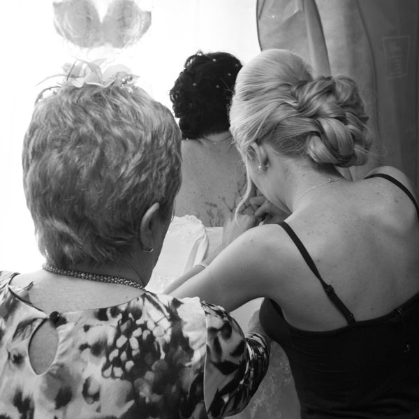 Bridesmaid and mother of the bride fastening brides dress black and white image Adwick Wedding Photographer