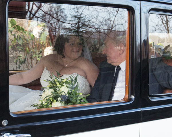 Bride and father of the bride looking at each other inside the wedding car before arriving at the ceremony