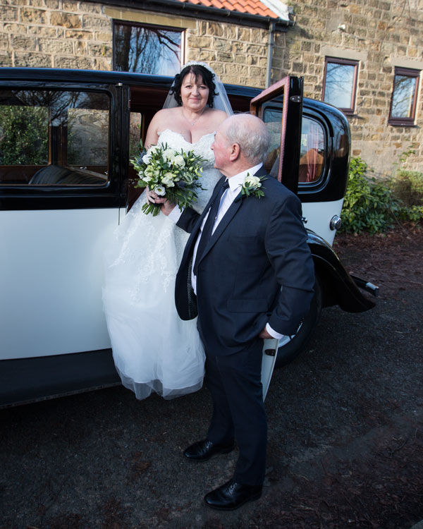 Father of the bride helping bride out of the car with purple and white bouquet Adwick upon Dearne