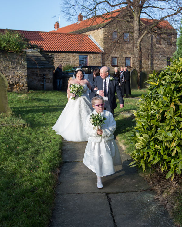 Bride walking down the aisle with her father and flower girl in front