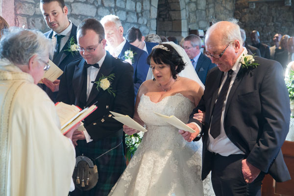 Bride groom and father of the bride singing a hymn at the front of church