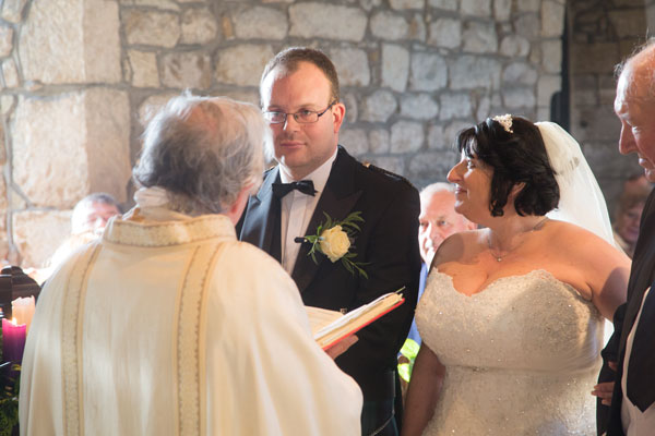 Bride looking at groom and smiling during the wedding ceremony St John the Baptist church Adwick upon Dearne