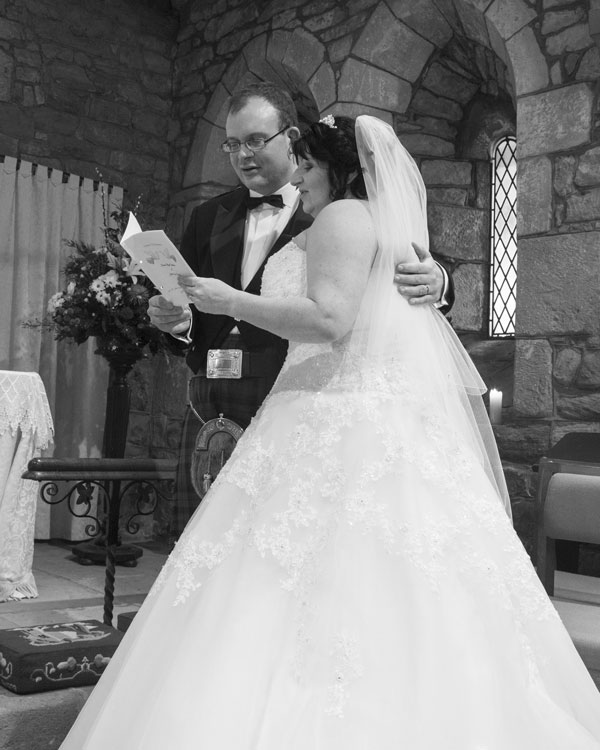 Bride and groom singing a hymn during their wedding service St john the baptist church Adwick upon Dearne