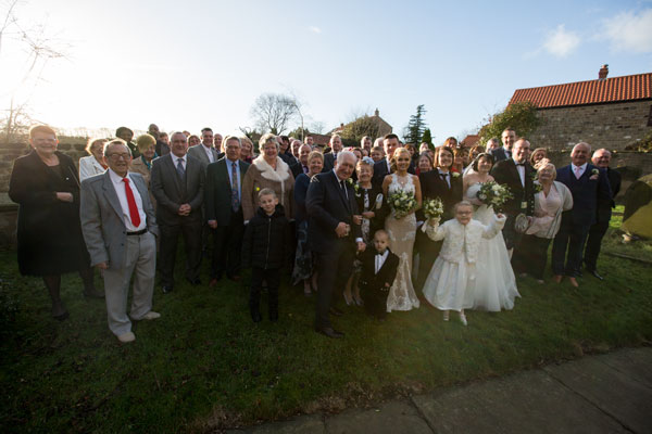 Whole wedding party in boxing day sunshine at St john the Baptist church Adwick upon Dearne