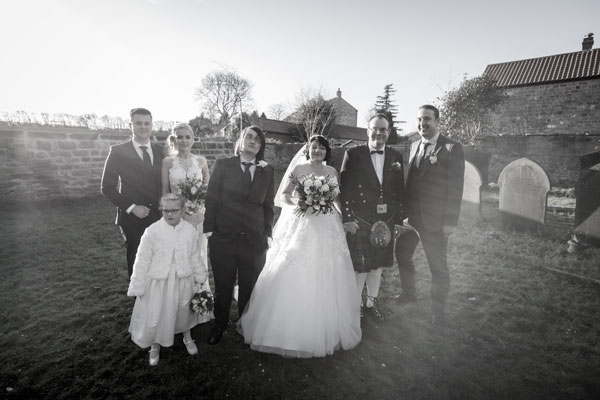 Bride Groom with Bridesmaids and Groomsmen in the grounds of St John the Baptist church Adwick upon Dearne in black and white