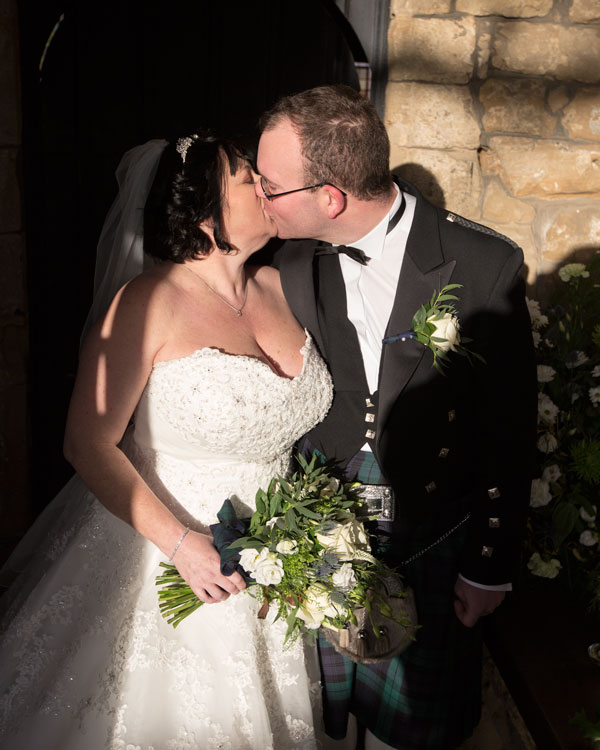 Bride and groom kissing in the doorway of St John the Baptist church Adwick upon Dearne