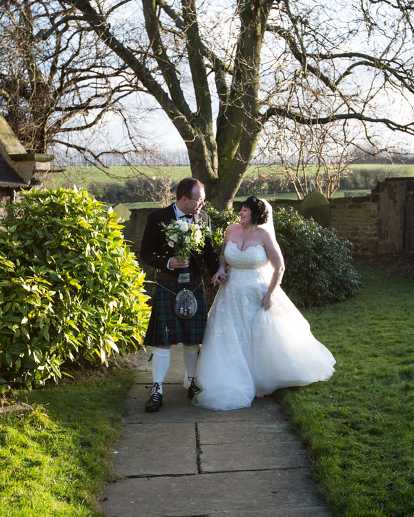 Newlyweds walking together holding hands with groom holding brides bouquet