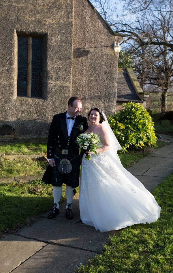 bride and groom in front of St John the Baptist Church Adwick upon Dearne looking at camera