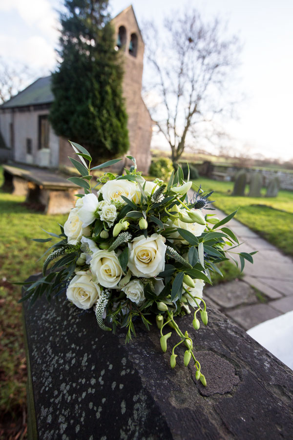 Brides bouquet on stone wall in front of St John the Baptist church Adwick upon Dearne