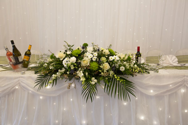 Green table flowers against a twinkle backdrop on the top table Pastures Lodge Mexborough