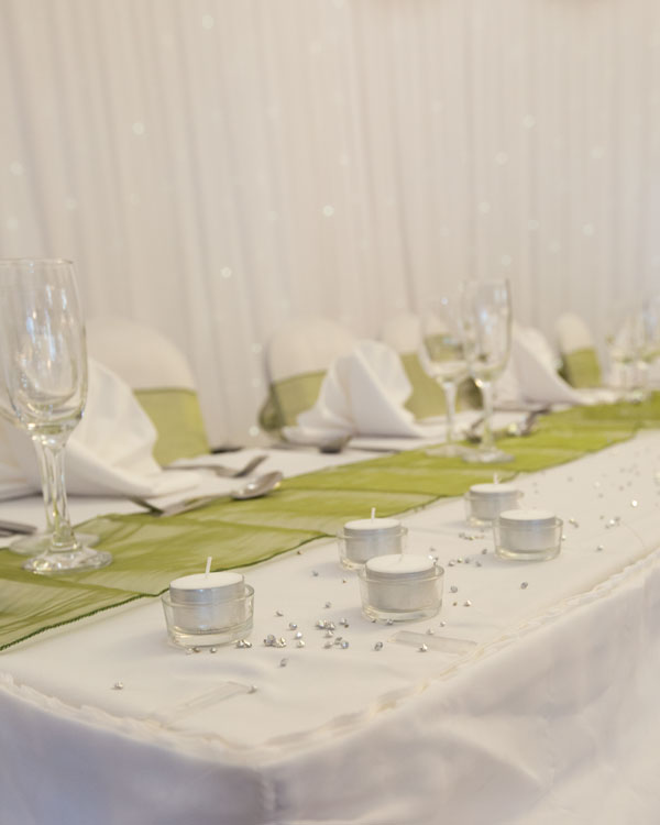 Tea lights decorating the top table with green table runner and chair sashes Pastures Lodge Mexborough
