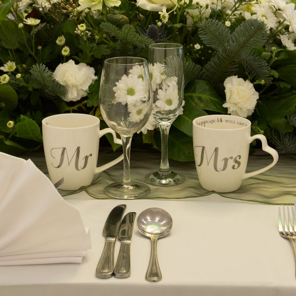 Mr and Mrs cups on the top table against green and white flower arrangement Pastures Lodge Mexborough