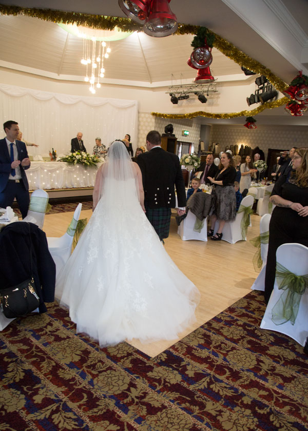Bride and groom walking into Pastures Lodge on boxing day with wedding and Christmas decorations