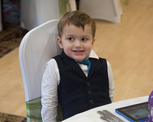 Boy sitting at table smiling Pastures Lodge Mexborough Adwick Wedding Photographer