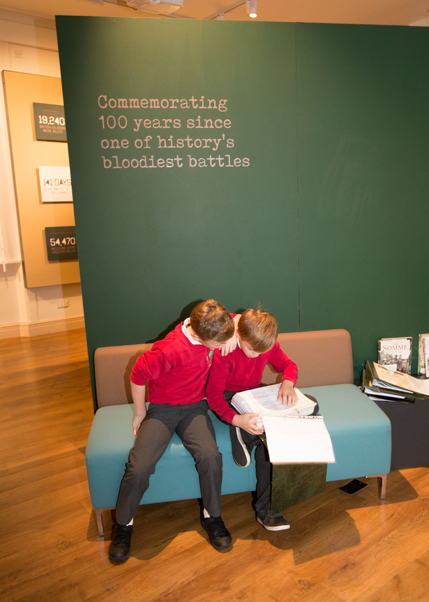 Two schoolboys in red uniform looking in a folder under the Stories of the Somme exhibition at Experience Barnsley
