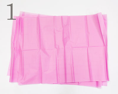 Eight sheets of pink tissue paper laying on top of each other on a white backdrop