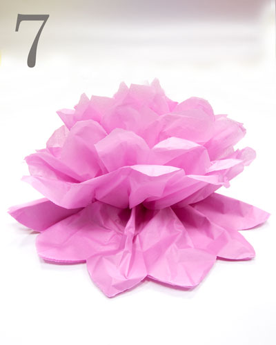 Pink tissue paper pompom completed at one side