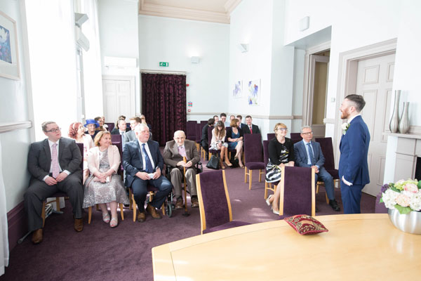 Groom standing at front of Leeds town hall ceremony room facing his guests