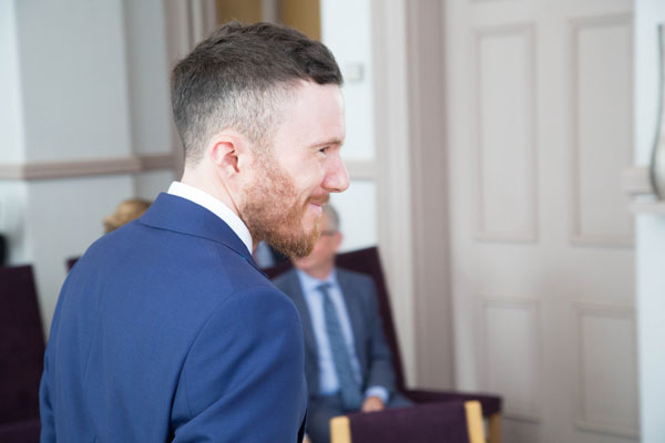 Groom in blue suit with ginger beard facing right in Ledds town hall ceremony room