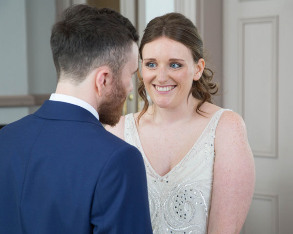Bride and Groom looking at each other and smiling during Leeds town hall wedding ceremony Leeds wedding photographer