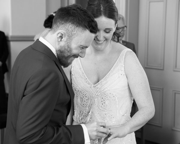 Black and white photograph Groom placing wedding ring on smiling brides finger Leeds wedding photographer