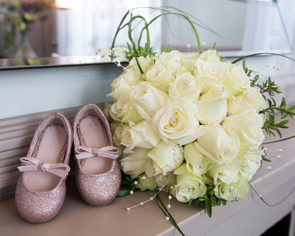 Birdal bouquet and flowergirls pink sparkly shoes on matlepiece in Leeds town Hall wedding ceremony room