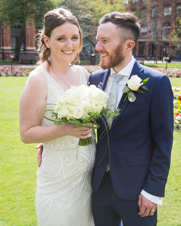 Groom looking at bride while Bride looks directly into the camera holding her bouquet Park Square Leeds
