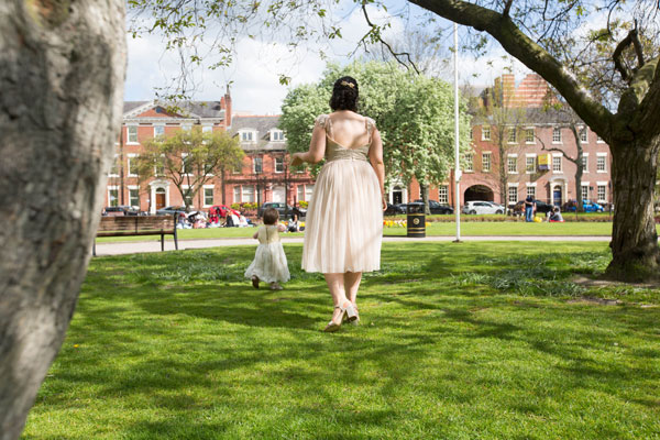 Bridesmaid watching flowergirl walking away from camera Park Square Leeds